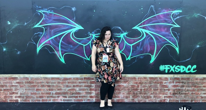 sam posed in front of painted vampire bat wings