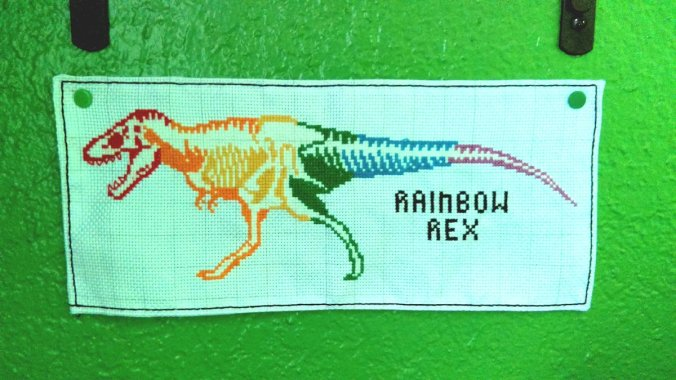 "cross-stitch dinosaur skeleton in rainbow colors with caption ""rainbow rex"""