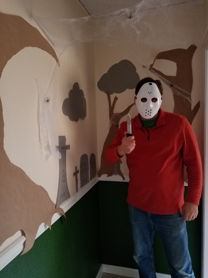 husband in Friday the 13th ski mask in front of hallway decorations